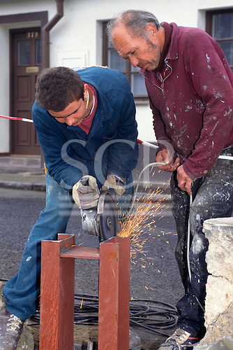 Roudnice, Czech Republic. Railway maintenance crew with angle grinder cutting steelwork.