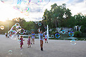 Spain - Barcelona - Children playing with soap bubbles in the Parc de la Ciutadella, onf of the major parcs in town.