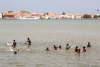 Senegal, Saint Louis.  Senegalese Boys Swimming in the River Senegal, Saint Louis River Front in Background.
