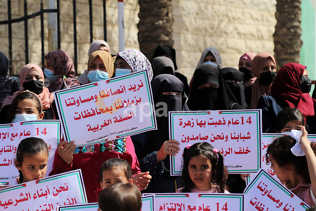 Palestinian employees of the security services -2005, take part in a protest to demand return to their works and their rights, marking International Workers' Day, in front of the Council of Ministers headquarters, in Gaza city, on May 02, 2021. Since the Palestinian division in 2007, the Palestinian Authority cut the salaries of these employees for various periods, ranging from 4 months to a year and a half, then returned to pay them a flat salary of 1,500 shekels (about $ 450) only under the item of a social grant. Photo by Mahmoud Ajjour