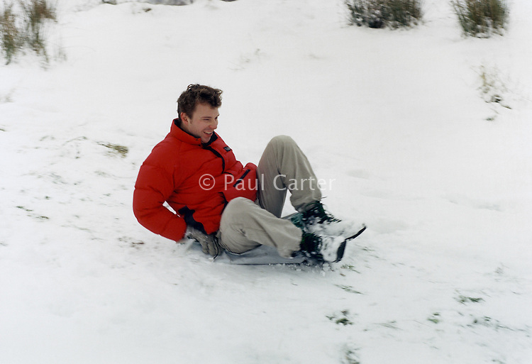 Young man sliding down a snowy slope on a make-shift sledge.