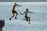 WEATHER PICTURE WALES<br /> Pictured: Two boys jump off the promenade wall in Mumbles, south Wales UK. Tuesday 16 August 2016<br /> Re: High temperatures and sunshine experienced in most of the UK.
