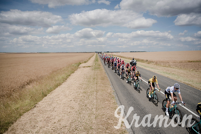 the peloton train rolling through the open fields with white jersey / best young rider Wout van Aert (BEL/Jumbo - Visma) escorting teammate / yellow jersey / GC leader Mike Teunissen (NED/Jumbo-Visma)<br /> <br /> Stage 3: Binche (BEL) to Épernay (FRA)(214km)<br /> 106th Tour de France 2019 (2.UWT)<br /> <br /> ©kramon