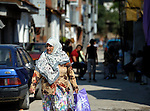 A Muslim Roma woman walks along a street in Suto Orizari, Macedonia. The mostly Roma community, located just outside Skopje, is Europe's largest Roma settlement. .