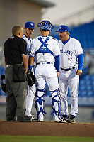 Dunedin Blue Jays pitching coach Mark Riggins (29) talks relief pitcher Jared Carkuff (19), catcher Mike Reeves (7) and umpire J.C. Velez during a game against the Clearwater Threshers on April 8, 2017 at Florida Auto Exchange Stadium in Dunedin, Florida.  Dunedin defeated Clearwater 12-6.  (Mike Janes/Four Seam Images)