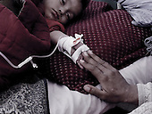 Kabul, Afghanistan<br /> November 2001<br /> <br /> Indira Ghandi children's hospital.Omidullah, 18 months old who is suffering from menigitis touches her mothers hand for comfort. They come from Dako Mirbachakot northern Afghanistan. The girl was admitted to the emergency room just hours prior to the image being made.