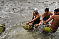 Young contraband smugglers pull gas cylinders out of the river Tachira on the Colombia-Venezuela border, 3 May 2006. Venezuelan gasoline, being 20 times cheaper than in Colombia, is the most wanted smuggling item, followed by food and car parts, while reputable Colombian clothing flow to Venezuela. There are about 25,000 barrels of gasoline crossing illegally the Venezuelan border every day. The risky contraband smuggling, especially during the rainy season when the river rises, makes a living to hundreds of poor families in communities on both sides of the frontier.