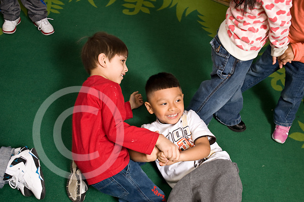 Education preschoool children ages 3-5 two boys playing wrestling roughhousing on rug horizontal