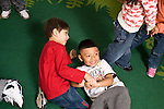 Education preschoool children ages 3-5 two boys playing wrestling roughhousing on rug horizontal