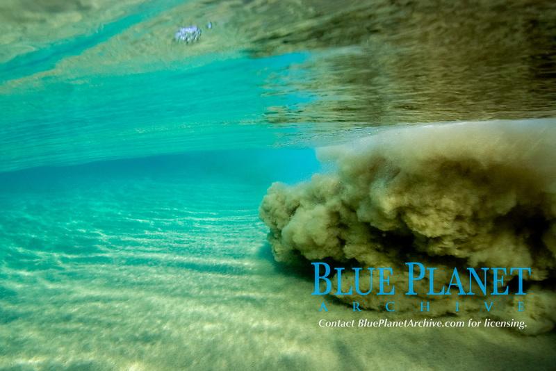 Breaking wave stirs up the sand underwater, Fernando de Noronha, Brazil