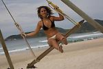 A young Argentinian woman tries out the surf swing on Praia do Rosa beach near Vida Sol e Mar Eco Resort, Santa Catarina, Brazil