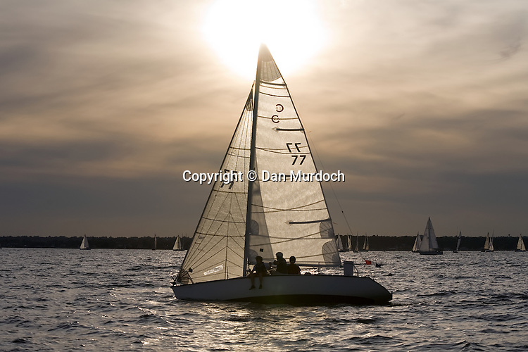 A sailboat mast points to the setting sun