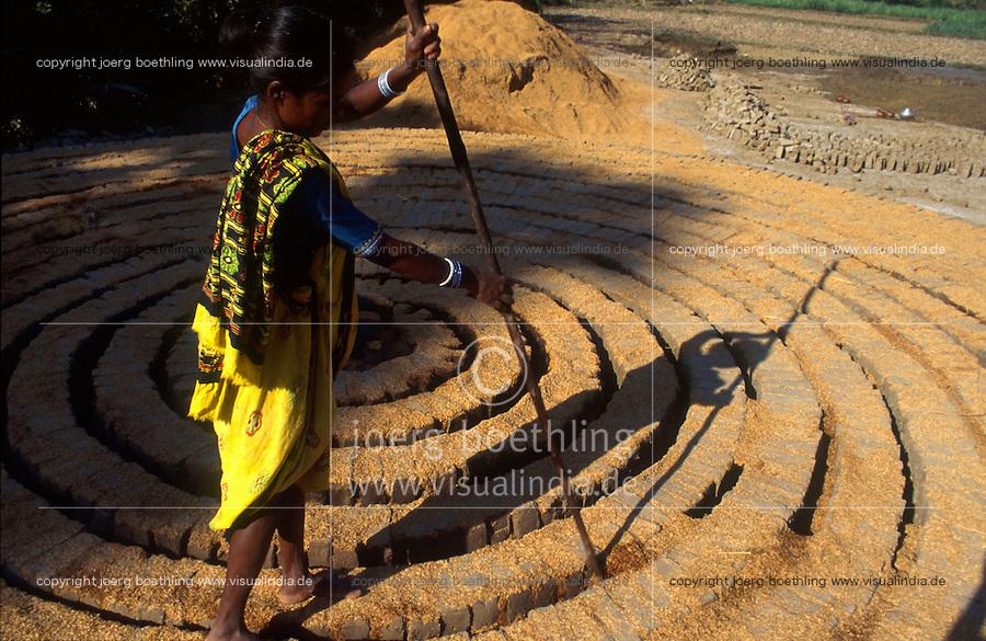INDIA Andhra Pradesh, woman applies rice chaff in brick oven for burning / INDIEN Andhra Pradesh, Frau streut Reisspreu als Brennstoff in Ziegelofen