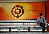 A man sits at a bus stop that is displaying a Bank of China logo in Shanghai, China...