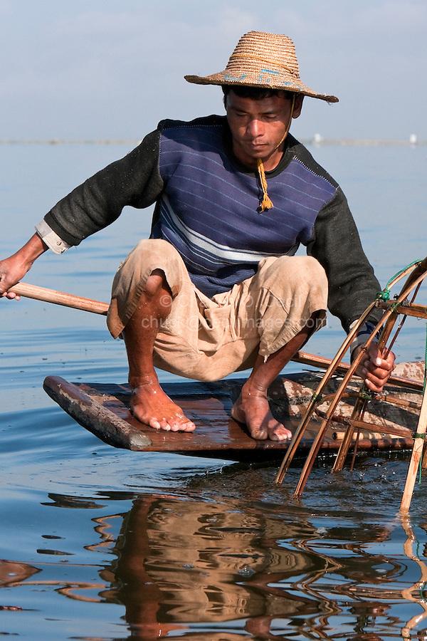 Myanmar, Burma.  Inle Lake Fisherman Looking for Fish While Placing his Net.