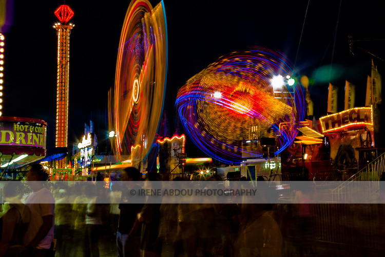 A slower shutter speed (8.0 sec) and small aperture (f/22) captures the full glory of these carnival rides in motion at the annual Montgomery County Agricultural Fair in Gaithersburg, Maryland.  The slower shutter speed also allows the photographer to express the movement of the fairgoers.