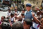 La lieutenant Silvia, sous-commandante de l'UPP du Morro da Formiga, est encerclée par les enfants à la sortie de l'école.