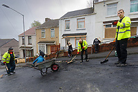 """Pictured: Locals and Council workers clean up in Waun-Wen Road in the Mayhill area of Swansea, Wales, UK. Friday 21 May 2021<br /> Re: Gangs of """"yobs"""" have been setting fire to cars and rolling them down a hill in Swansea, Wales, UK.<br /> South Wales Police said they attended """"large scale disorder"""" in the Mayhill area of the city on Thursday evening."""