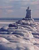Snowy owl visits the lower harbor breakwall lighthouse in Marquette Michigan on Lake Superior after a three day storm in January 1978.