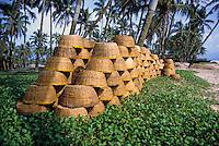 Stacks of fishing baskets drying on Colva Beach, Goa, India.