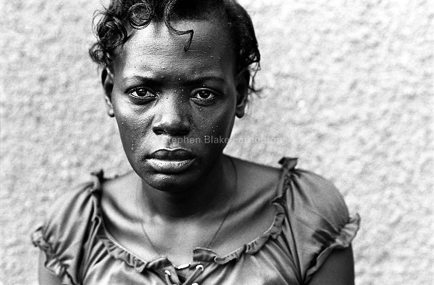 """Portrait of a woman HIV positive. This woman attends a support group in the town of Bugembe.  The group has been formed by people that are sick with the disease and is called """"Living with HIV."""" The name is to stress, not the fact that the individuals are infected, but how to now live their lives in a positive manner.  Uganda has an estimated 1.5 million people infected with HIV/AIDS. Bugembe, Jinja District, Uganda, Africa. June 2004 © Stephen Blake Farrington"""