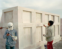 A grave builder checks his mobile phone in a coastal cemetery. The workers wear makeshift masks and sunglasses to protect themselves from the sun's glare, which bounces off the mussel-chalk they work with. They are building elaborate mausoleums for the newly rich middle class. These grave builders work from dawn til dusk, sleeping on site for months at a time.