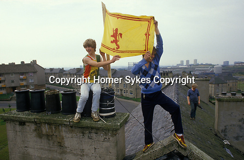 Glasgow, Scotland. 1980's<br /> Two young scallywags playing truant flutter the Rampant Red Lion, the Royal Flag of Scotland from their slate-roofed council tenements in the Blackhill estate. Their bad influence hovers in the background. <br /> <br /> The young man on the right  is wearing a pair of Nike Omega Flame  trainers and a Fred Perry Diamond jumper.