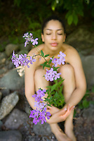 Young woman with eyes closed sitting close to purple flowers
