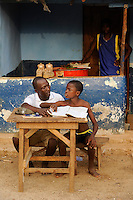 SIERRA LEONE, fishing village River No. 2, father and son doing home works for school / SIERRA LEONE , Fischerdorf River No. 2 am Western Area National Park  , Ibrahim Sankoh, und Sohn Nelson 12 Jahre, bei Schularbeiten