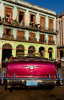 Classic 50s Buick colorful convertible auto in Havana Cuba Habana in front of old worn and colorful apartment buildings in downtown city