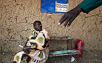 A woman with her baby is directed into a  polling station in Malakal, South Sudan. On 9th January 2011 Southern Sudan's people voted in a referendum on whether to become independent from the North..