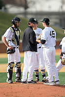 Wake Forest Demon Deacons assistant coach Matt Hobbs makes a pitching change during the game against the Miami Hurricanes at Wake Forest Baseball Park on March 21, 2015 in Winston-Salem, North Carolina.  The Hurricanes defeated the Demon Deacons 12-7.  (Brian Westerholt/Four Seam Images)