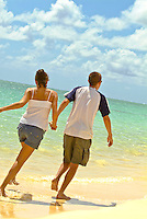 A couple holding hands, running and having fun at spectacular Lanikai Beach, near Kailua, Windward Oahu