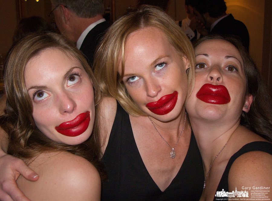 Three women playfully wear red wax lips as they vamp for the camera.