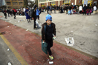 Pictured: A young boy walks alone as dozens of other migrants rest on the ground after disembarking at the port of Piraeus Friday 26 February 2016<br />Re: Hundreds of refugees that crossed the border from Turkey to the Greek islands, have arrived at the port of Piraeus near Athens, Greece