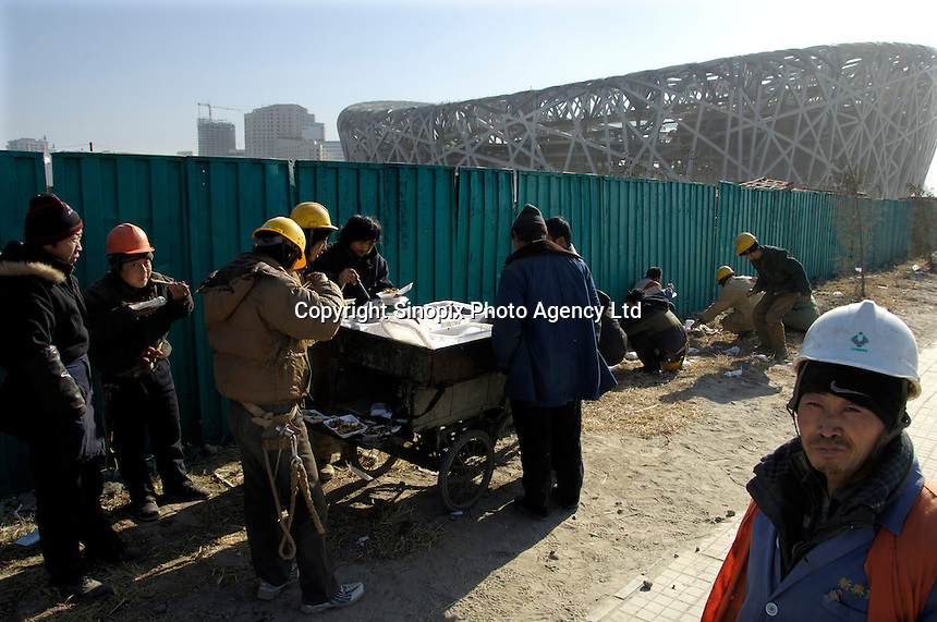 Chinese workers have lunch at the construction site of the National Stadium known as the Bird Nest for the Beijing 2008 Olympics Games in Beijing, China..