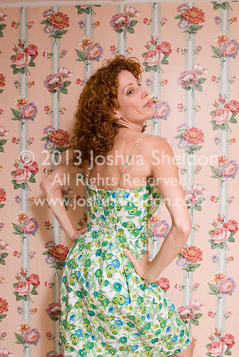 Redheaded woman wearing floral in front of pink floral wallpaper