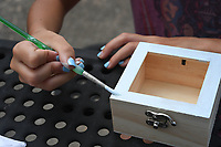 Anna Stewart, 9, paints a wooden box Monday July 19, 2021 at Wilson Park in Fayetteville. Visit nwaonline.com/21000720Daily/ and nwadg.com/photo. (NWA Democrat-Gazette/J.T. Wampler)