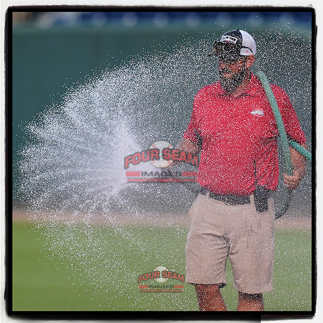 Head groundskeeper Greg Burgess of the Greenville Drive sprays the infield before a game against the Asheville Tourists on Tuesday, June 1, 2021, at Fluor Field at the West End in Greenville, South Carolina. (Tom Priddy/Four Seam Images) #MiLB #baseball