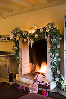 A group of beautifully wrapped presents sits in front of the large stone fireplace decorated for Christmas with sprigs of spruce and glass baubles