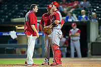 North Carolina State Wolfpack catcher Andy Cosgrove (2) shows trainer Anthony Sandersen and associate head coach Chris Hart where he was hit in the throat by a foul ball during the game against the North Carolina Tar Heels in Game Twelve of the 2017 ACC Baseball Championship at Louisville Slugger Field on May 26, 2017 in Louisville, Kentucky.  The Tar Heels defeated the Wolfpack 12-4 to advance to the semi-finals.  (Brian Westerholt/Four Seam Images)