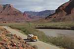 Van pulling whitewater rafts on Highway 128 wth Fisher Towers and the Colorado River near Moab, Utah, USA.