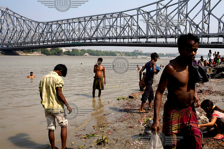 Men washing and bathing on the banks (ghats) of the Hooghly River where it flows under the Howrah Bridge.