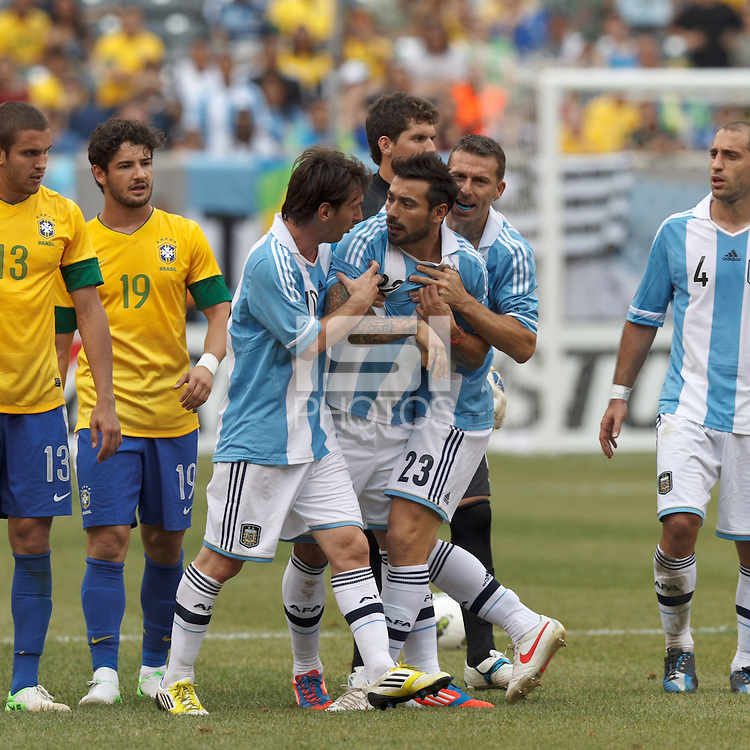 Argentina forward  Lionel Messi (10) and Argentina defender Hugo Capagnaro (23)usher red card ejected Argentina substitute forward  Ezequiel Lavezzi (22). In an international friendly (Clash of Titans), Argentina defeated Brazil, 4-3, at MetLife Stadium on June 9, 2012.