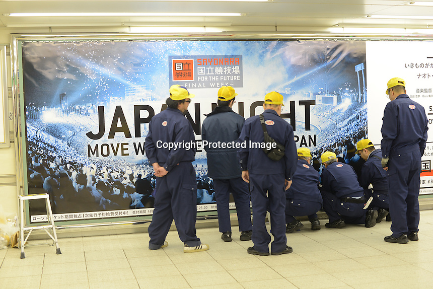 Workers at a poster advertising the demolition of the old Olympic stadium as a new one is built for the 2020 Olympics. <br /> April-2014