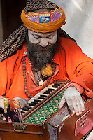 Pashupatinath, Nepal.  Sadhu (Holy Man) at Nepal's Holiest Hindu Temple, Playing Accordion-like Instrument.