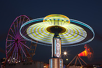AUGUSTA, NJ - AUGUST 13: The colorfully illuminated Gentle Giant Ferris Wheel and Yo Yo spin against the night sky during the New Jersey State Fair on August 13, 2010 at the Sussex County Fairgrounds, Augusta, New Jersey