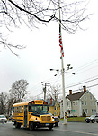 NEWTOWN, CT. 18 December 2012-121812SV01-A school bus passes by the flagpole on Main Street in Newtown Tuesday. Newtown students returned to school today with the exception of Sandy Hook..Steven Valenti Republican-American