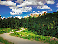 Rock outcrop, puffy clouds, and road in Uncompahgre National Forest, Colorado.