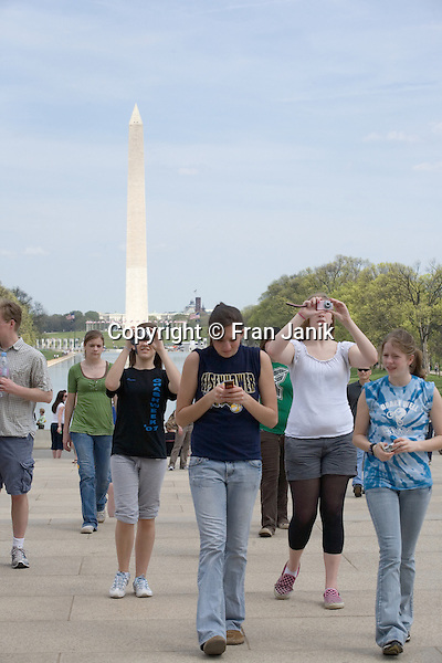 Several young women raise their cameras to photograph the Lincoln Monument in Washington D.C.. The reflecting pool and the Washington Monument can be seen in the backround.